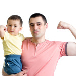 man and his son kid showing muscles