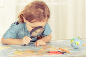 little boy considering a world map with a magnifying glass